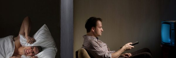 Man at night can't fall asleep because of the noisy neighbor