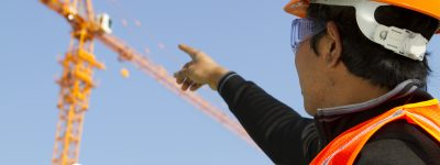 Engineer checking work plan on location site. Horizontal image asian engineer wearing orange safety vest and helmet under construction checking plan with yellow crane on the background and blue sky